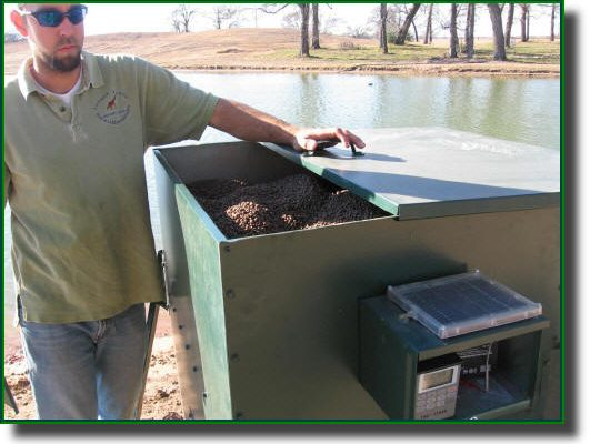 An automatic fish feeder is checked for proper operation.