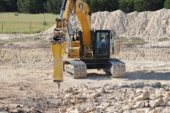 Breaking up rock with the excavator mounted hydraulic hammer.  When dealing with rock many obstacles and challenges come into play and quite often one must try different approaches in order to acheive the goal.