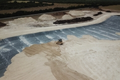 Cover dirt being spread by small dozer.