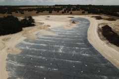 Liner is complete.  Cover dirt is stockpiled on shoreline and small dozer is beginning to spread the cover dirt.