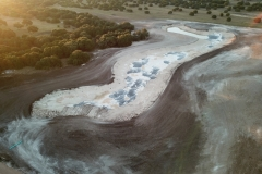 Aerial view of semi completed project.  The darker soils along the shore line is top soil so that grass can be establish.  The liner is visible in the center of the lake site.